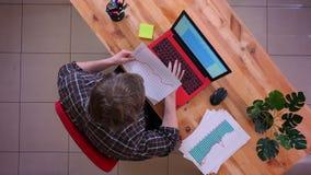 Lanzamiento del top del primer del hombre de negocios caucásico joven que mecanografía en el ordenador portátil en el escritorio  almacen de metraje de vídeo