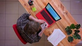 Lanzamiento del top del primer del hombre de negocios caucásico joven que mecanografía en el ordenador portátil en el escritorio  metrajes