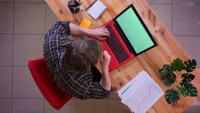 Lanzamiento del top del primer del hombre de negocios caucásico joven que mecanografía en el ordenador portátil y el café de cons almacen de video