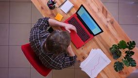 Lanzamiento del top del primer del hombre de negocios caucásico joven que mecanografía en el ordenador portátil y que tiene una l almacen de video