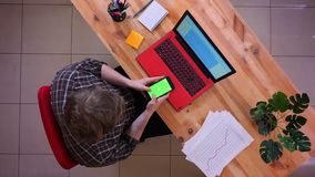 Lanzamiento del top del primer del hombre de negocios caucásico joven que mecanografía en el teléfono que se sienta delante del o almacen de metraje de vídeo