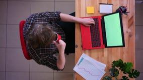 Lanzamiento del top del primer del hombre de negocios caucásico joven que trabaja en el ordenador portátil con la pantalla verde  metrajes