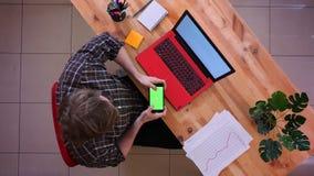 Lanzamiento del top del primer del hombre de negocios caucásico joven que usa el teléfono con la pantalla verde de la croma que s almacen de metraje de vídeo