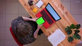 Lanzamiento del top del primer del hombre de negocios caucásico joven que usa la tableta con la pantalla verde de la croma que se almacen de video