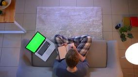 Lanzamiento del top del primer del hombre de negocios joven que trabaja y que toma notas usando el ordenador port?til con la pant almacen de video