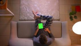 Lanzamiento del top del primer del hombre joven que hojea en la tableta con la pantalla verde de la croma mientras que se sienta
