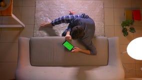 Lanzamiento del top del primer del hombre joven que mira un anuncio la tableta con la pantalla verde mientras que se sienta en el almacen de metraje de vídeo