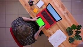 Lanzamiento del top del primer del movimiento en sentido vertical caucásico joven del hombre de negocios en la tableta con la pan metrajes