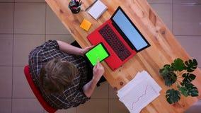 Lanzamiento del top del primer del movimiento en sentido vertical caucásico joven del hombre de negocios en la tableta con la pan almacen de metraje de vídeo