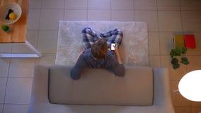 Lanzamiento del top del primer del varón caucásico joven que ve la TV el sentarse en el piso y el usar de un app en el teléfono c almacen de video