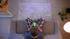 Lanzamiento del top del primer del varón ocasional vestido joven que mira un anuncio en el teléfono que se sienta en el sofá dent metrajes