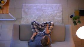 Lanzamiento del top del primer del varón ocasional vestido joven que tiene una llamada video en el teléfono mientras que se sient metrajes