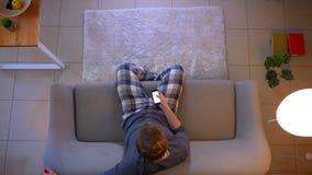 Lanzamiento del top del primer del varón ocasional vestido joven que ve la TV el sentarse en el sofá y el usar de un app en el te metrajes