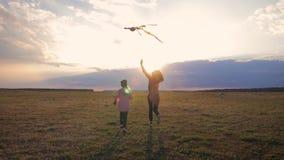 Lanzamiento feliz de la hija de la madre y del niño de la familia una cometa en prado en la puesta del sol Tiempo divertido de la almacen de video
