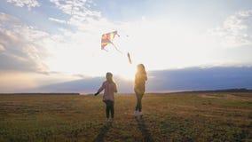 Lanzamiento feliz de la hija de la madre y del ni?o de la familia una cometa en prado en la puesta del sol Tiempo divertido de la metrajes