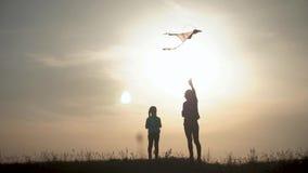 Lanzamiento feliz de la hija de la madre y del ni?o de la familia una cometa en prado en la puesta del sol Tiempo divertido de la almacen de video