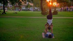 Lanzamiento hermoso del varón joven y de la hembra atléticos que realizan una actitud del acroyoga en el parque con la puesta del almacen de metraje de vídeo