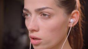 Lanzamiento macro del primer del atleta atractivo joven de sexo femenino en sus ambientes y la mirada adelante con la expresión m metrajes