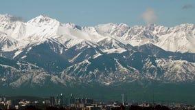 Lanzamiento panorámico de montañas nevosas y ciudad de Almaty, Kazajistán metrajes