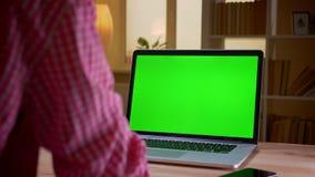 Lanzamiento trasero de la opini?n del primer del hombre de negocios joven indio que usa el ordenador port?til con la pantalla ver metrajes