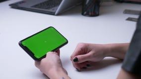 Lanzamiento trasero de la opini?n del primer de la mano femenina que juega un anuncio video en el tel?fono con la pantalla verde  metrajes