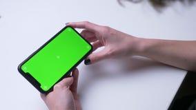 Lanzamiento trasero de la opini?n del primer de la mano femenina que juega un anuncio video en el tel?fono con la pantalla verde  almacen de metraje de vídeo