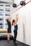 Lanzar la bola de medicina en el gimnasio Imagen de archivo