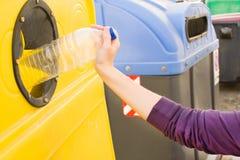 Lanzar una botella en el envase de reciclaje Imagen de archivo