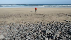 Young man rides a bicycle on big stones towards a sand beach on Canary Islands. Lanzarote, Atlantic ocean. Lanzarote, Atlantic ocean. Young man rides a bicycle stock video