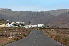 Lanzarote, estrada que do deserto isso conduz a uma casa de campo pequena Fotos de Stock Royalty Free