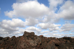 Lanzarote island landscape. Scenic rocky volcanic landscape of Lanzarote island with blue sky and cloudscape background Royalty Free Stock Images