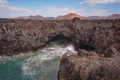 Lanzarote landskap Kustlinje för Los Hervideros, lavagrottor, klippor och krabbt hav Den Unidentifiable turisten är i bakgrunden arkivfoton