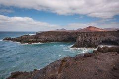 Lanzarote landskap Kustlinje för Los Hervideros, lavagrottor, klippor och krabbt hav Den Unidentifiable turisten är i bakgrunden arkivbild