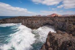 Lanzarote landskap Kustlinje för Los Hervideros, lavagrottor, klippor och krabbt hav Den Unidentifiable turisten är i bakgrunden royaltyfri foto
