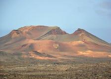 Lanzarote Lavafelder beherrscht durch enormen Vulkan stockfotografie
