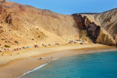 Group of people relaxing on Papagayo beach on the island of Lanzarote, Spain Stock Image