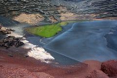 Lanzarote, praia vulcânica do preto cercada pelo colo Imagens de Stock