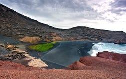 Lanzarote, praia vulcânica do preto cercada pelo colo Imagem de Stock