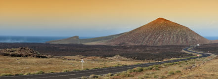 Lanzarote volcanoe, Spain. Volcanic landscape and winding road in Lanzarote, the Canary islands, Spain. Panoramic image Royalty Free Stock Photo