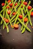 Lanzas verdes frescas del espárrago con los tomates asados Fotografía de archivo libre de regalías