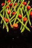 Lanzas verdes frescas salteadas del espárrago con los tomates Fotos de archivo libres de regalías