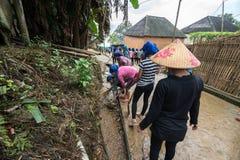 Lao Cai, Vietnam - 30 agosto 2017: Volontari - gli agricoltori che puliscono la strada del villaggio su un'attività sociale regol Fotografia Stock Libera da Diritti