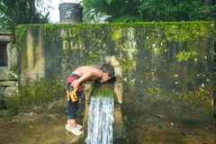 Lao Cai, Vietnam - Sep 7, 2017: Ethnic minority child drink water from small spring downstream from mountain in Y Ty, Bat Xat dist. Rict Stock Photos