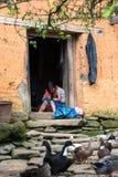 Lao Cai Vietnam - September 7, 2017: Den etniska flickan broderar på dörr på hennes hus med höns på jordning i Y Ty, det slagträX Fotografering för Bildbyråer