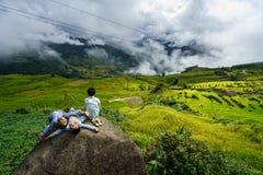 Lao Cai Vietnam - September 7, 2017: Den terrasserade risfältet på plockningsäsong med barn som sitter på, vaggar i Y Ty, det sla Royaltyfria Foton