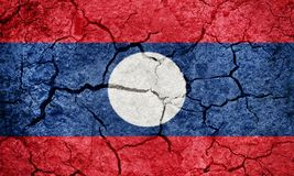 Lao People`s Democratic Republic flag. On dry earth ground texture background stock photography