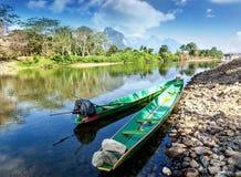 Lao Traditional-Boote auf dem Ufer von einem Gebirgsfluss Stockfotos