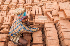 Daily laobour. An worker carrying bricks in a dusty environment Stock Images
