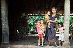 laofamilj med modern och gulliga ungar som väntar under deras styltahus royaltyfri foto