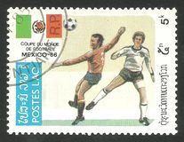 Football play scene and flag. Laos - CIRCA 1985: Stamp printed by Laos, Multicolor edition offset printing on topic of Football World Cup, shows football play Royalty Free Stock Image